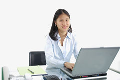 First Job Typing. A young college intern at her desk typing on a laptop royalty free stock photos