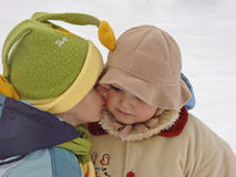 First kiss 1. Little girl being kissed in snow Stock Photo