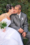 First kiss. Kissing bride and groom portrait on a bench Stock Photography