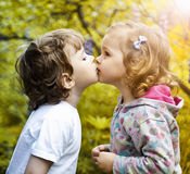 First kiss. Little boy kissing a girl Royalty Free Stock Photography