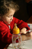 First learning. Little girl trying to learn with bottle on side - focus on milk bottle Royalty Free Stock Photos