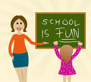 First lesson: School is fun!. Situation at school: Teacher shows little girl that school can be fun Royalty Free Stock Photo