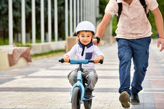 First lessons bicycle riding. Father teach his son to ride a bike. Happy childhood concept Stock Images