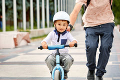 First lessons bicycle riding. Father teach his son to ride a bike. Happy childhood concept Stock Photos