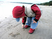 First letter ever. Small child writing on sand at a beach Royalty Free Stock Photography