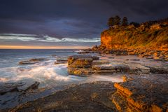First light at Avalon Beach. Rich golden orange tones of light striking the cliff faces and rocks stock images