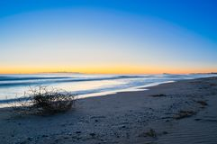 First light of day on a clear morning at the beach of Valencia. Magical bluish sunrise with orange glow background royalty free stock photos