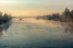 The fog rises from the river adda shortly after dawn. At the first light of day when the temperature begins to rise, the fog rises from the river Adda in royalty free stock images