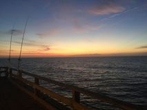 First Light. A Peaceful beginning of the day fishing on an Atlantic Ocean Pier Stock Photo