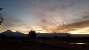 The first light of sunrise on the volcanoes of the Andean cordillera, Atacama Desert, Chile. Sunrise lights in the arid and desolate landscape of the Atacama royalty free stock images