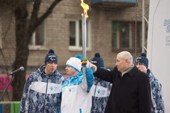 First lighted torch held Tver Mayor Alexander Korzin and athlete Stock Photography