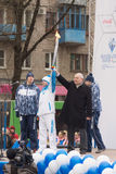 First lighted torch held Tver Mayor Alexander Korzin and athlete Royalty Free Stock Images