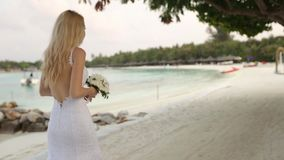 First look of young wedding couple. Bride goes to wedding ceremony on romantic tropical island on the white sand beach. Near azure lagoon ocean on Maldives stock video footage