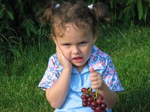First losing teeth. Little girl eating grapes , siting in the grass-plot and felt teeth pain Royalty Free Stock Photos