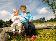First Love. Adorable little toddler boy and girl sitting on a bench, holding each other (3 and 1 years old Royalty Free Stock Images