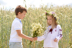 First love concept. Boy giving a girl bunch of wild flowers. Stock Photography