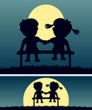 First Love in the Moonlight. Silhouettes of two kids in love for the first time sitting on a bench in the moonlight. Background and banner (fits perfectly as a Royalty Free Stock Photos