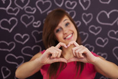 First love. Woman showing heart shape with her hands Royalty Free Stock Photo