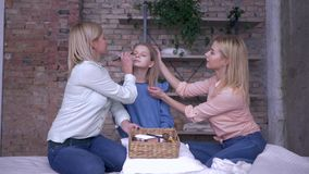 First make up, merry mom with adult daughter put cosmetics on face of little pretty girl using special brushes and and stock footage