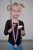 The first medal. Little gymnast girl with medal and flower after competition royalty free stock image