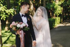 First meet of bride and groom on their wedding. Happy smile bride in veil touches the shoulder of groom in with bouquet stock image