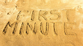 First minute. Words first minute handwritten on the sandy beach Royalty Free Stock Photos