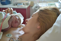 The first moments of mother and newborn after childbirth. Mother holding her newborn baby child after labor in a hospital stock photography