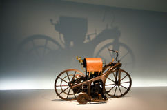The first motobike, pioneers of auto. Archaic vehicle Reitwagen. Neutral background and large shadow Stock Photos