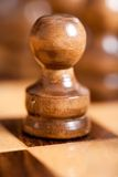First move. Pawn in front of chess pieces on a board, shallow depth of field Royalty Free Stock Image