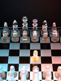 The First Move. A glass chess set showing an opening move with king's pawn Royalty Free Stock Photo