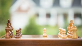 First move over wood chessboard. Real estate sale home savings loans market. First move over a wood chessboard. Closeup chess game figures isolated outside home Royalty Free Stock Photos