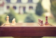 First move over wood chessboard. Real estate sale home savings loans market. First move over a wood chessboard. Closeup chess game figures isolated outside home Stock Photo