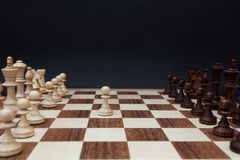 First move by white pawn on the center of board. Chess board on a black background. Stock Photography