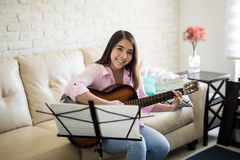 First music lessons. Attractive young woman learning to play guitar by herself with some music sheets in the living room Stock Image
