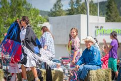 First Nations dancers wave to crowds from parade float. Williams Lake, British Columbia/Canada - July 2, 2016: First Nations children, elders, and dancers wave Royalty Free Stock Photos