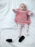 First pair of shoes. Portrait of a baby girl dressed in a pink dress lying down Stock Photos