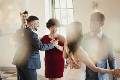 First Partner Dance At Millennial Wedding. First partner dance at a wedding. All of the couples are dancing together along with the bride and groom Royalty Free Stock Photography