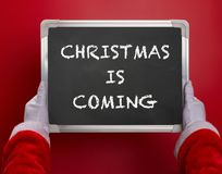 First person angle view of Santa Claus holding a black chalk board written with CHRISTMAS IS COMING on red. Background Stock Photo