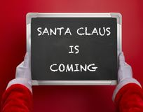 First person angle view of Santa Claus holding a black chalk board written with SANTA CLAUS IS COMING on red. Background Royalty Free Stock Photo