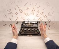 First person perspective elegant hand typing with flying letters concept. First person perspective elegant hand writing on typewriter with flying letters Royalty Free Stock Photography