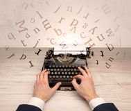First person perspective elegant hand typing with flying letters concept. First person perspective elegant hand writing on typewriter with flying letters Stock Photos