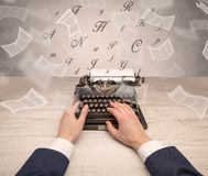 Hand typewriting with flying documents around Stock Image