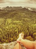 First person perspective shot from hiker sit at edge of cliff stock image