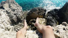 First person perspective of young man sitting on rock cliff edge above sea.  stock video