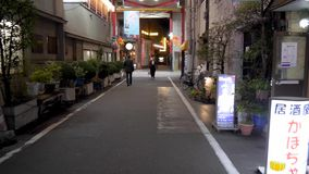First person POV walking down a side street at night in Tokyo Japan. Neon signs and restaurants line the alleyway stock footage