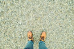 First person view on a boots on chippings. Concept stock photography