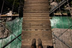 First person view on feet on suspended bridge above water in France stock images