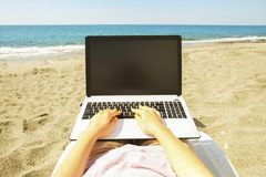 Young blonde hair woman working on laptop at the beach on sunny day. Close up of female hands typing on white notebook computer la. First person view. Female Stock Photos