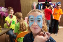First person view of girl with face paint. Close up view of girl getting her face painted while seated in a dressing room Royalty Free Stock Photography