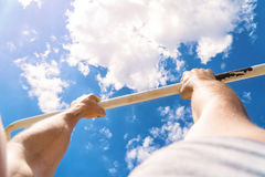 First-person view of the horizontal bar. The guy pulls up on the bar. Workout outdoors. Blue sky on blackground.  Stock Photo